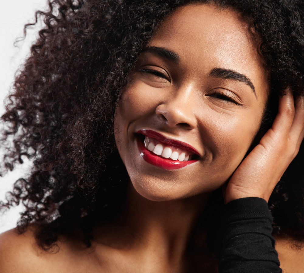 happy smiling black woman with afro curly hair